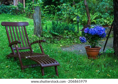 tranquil scene of a garden chair with flowers - stock photo