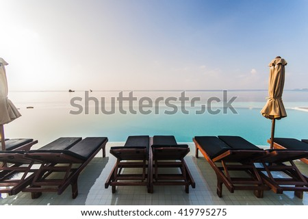 Tranquil scene of a swimming pool and beach with palm trees and white sand