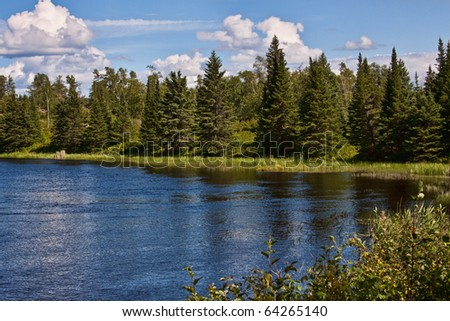 Tranquil scene of blue sky with lake and forest - stock photo