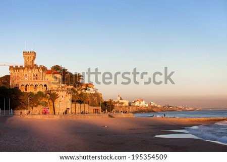 Tranquil scenery by the Atlantic Ocean, Tamariz Beach overlooked by a castle at sunset in resort town of Estoril in Portugal. - stock photo