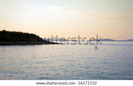 Tranquil scenery of a man paddling on his surfboard in the sunset Croatia. Space for text.