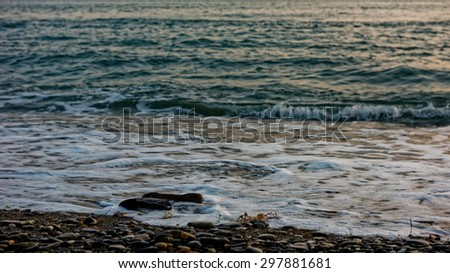 Tranquil sea washing pebble coast on a sunny day - stock photo