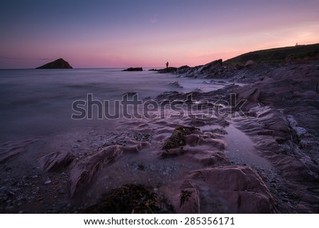 Tranquil seascape at twilight with fisherman silhouette on rocky beach - stock photo