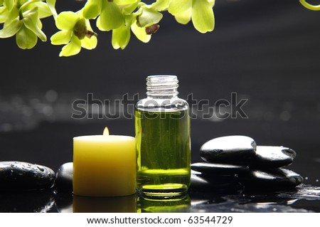 tranquil spa scene - massage oil and candle on black stones with green orchid - stock photo