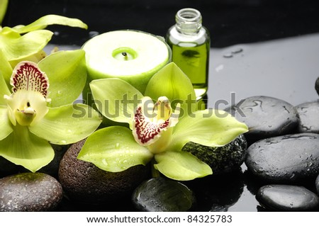 tranquil spa scene –massage oil and candle with green orchid - stock photo