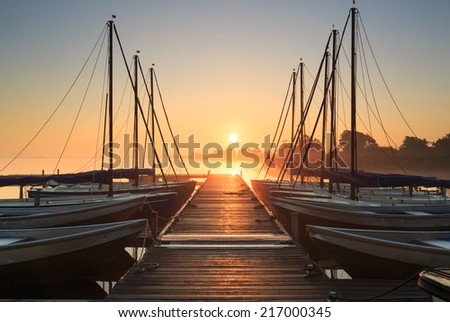 Tranquil sunrise over a wooden jetty with sailing boats. - stock photo