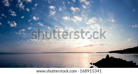 Tranquil sunrise panorama of lake and clouds - stock photo