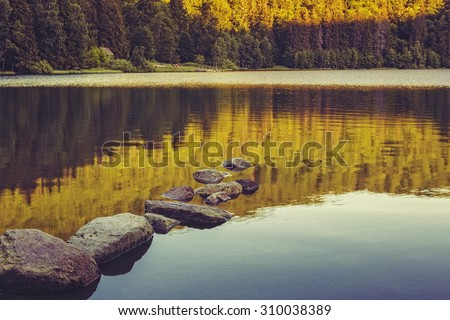 Tranquil sunset scenery with sunken rocks and forest reflections on the calm surface of the Saint Ana (Sfanta Ana) lake, Romania. Toned edit. - stock photo