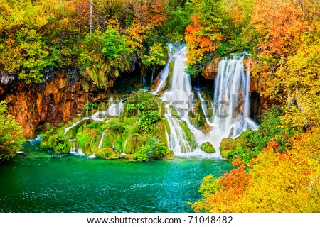 Tranquil waterfall scenery in the middle of autumn forest, HDR technique - stock photo