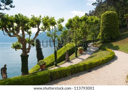 Tranquil winding path in the Villa Balbianello garden along the shore of lake Como, Italy - stock photo
