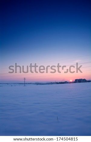 Tranquil winter scenery with town in the background - stock photo