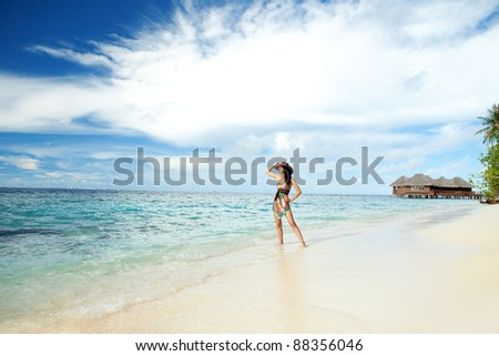 Tranquil woman on the tropical beach with bungalows - stock photo