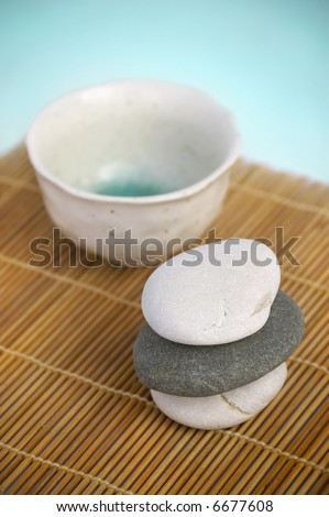 Tranquil Zen style scene. Ceramic cup and pebbles on bamboo mat
