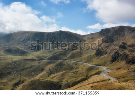Transalpina road. Transalpina is one of the highest roads passing the Carpathians in Romania. Layers of haze cover the mountains peaks at sunset. Low key, spot lighting, and rich Old Masters - stock photo