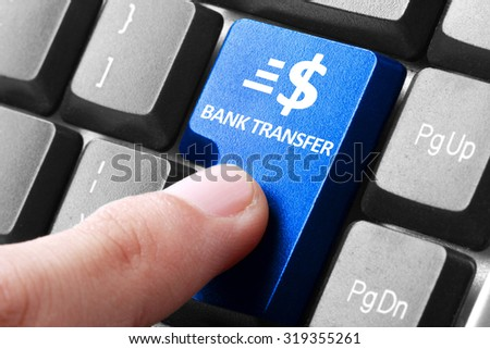 Transfering online. gesture of finger pressing Bank Transfer button on a computer keyboard - stock photo