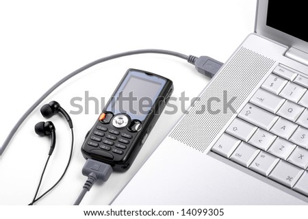 Transferring music from laptop to mobile phone - stock photo