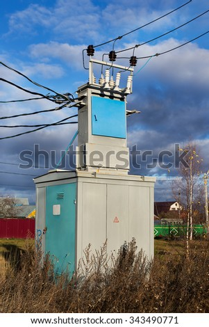 Transformer of transmission line locating in the village - stock photo