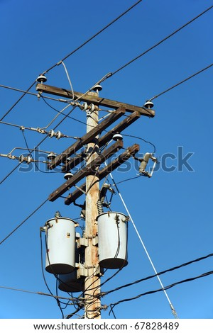 Transformers of an electrical post with powerlines against bright blue sky. - stock photo