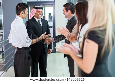 translator introducing arabian businessman to business partners - stock photo