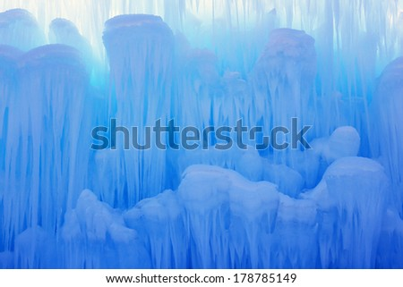Translucent blue icicles in a frozen ice wall. - stock photo
