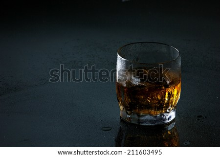 translucent brown-gold whiskey with ice cubes in glass on misted dark grey surface  with place for your text - stock photo