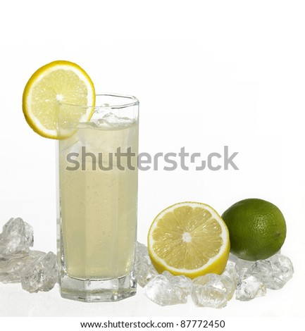 translucent soft drink drink in light back with lemon fruits and ice cubes - stock photo
