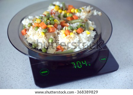 Translucent white plate with rice and vegetables is at home kitchen electronics scales to count calories in food. Photo closeup - stock photo