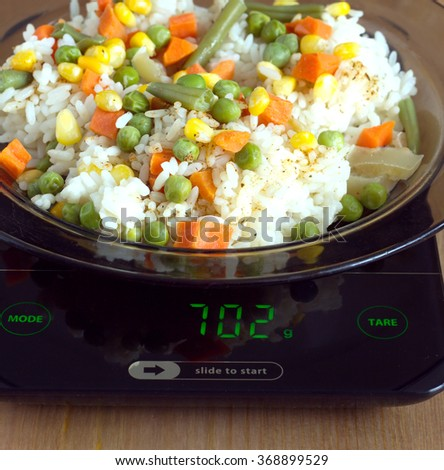 Translucent white plate with rice and vegetables is at home kitchen electronics scales to count calories in food on wooden table. Front view closeup - stock photo