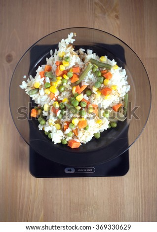 Translucent white plate with rice and vegetables is at home kitchen electronics scales with empty display on wooden table. Top view closeup - stock photo