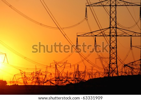 transmission tower   against the sun during sunset - stock photo