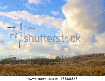 Transmission tower, or electricity pylon, in a field in front of a cloudy sky - stock photo