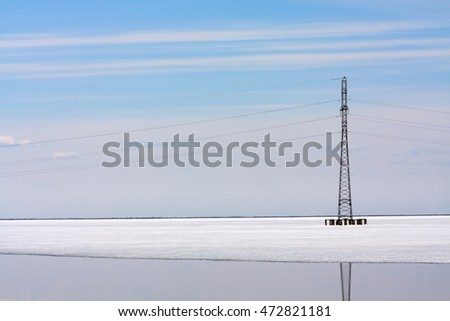 Transmission tower standing in loch thawing by spring
