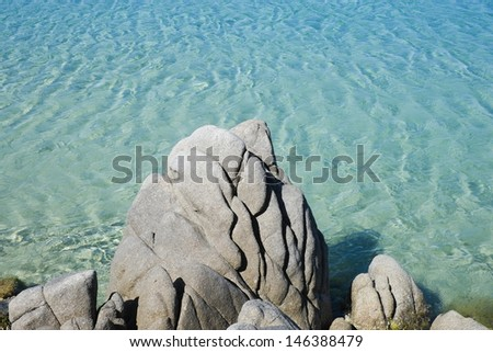Transparent and green water with rock along the coast in Chia, Sardinia, Italy - stock photo