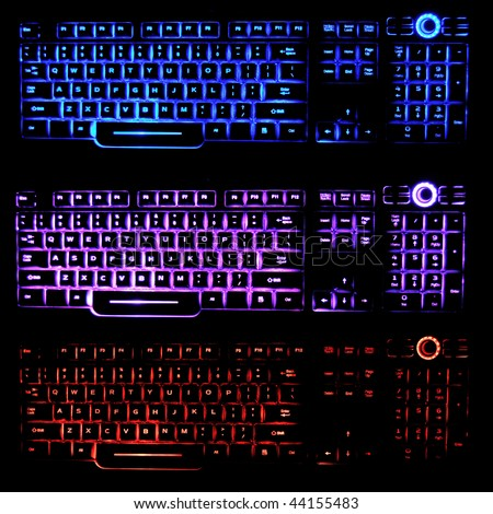 Transparent, blue, pink, and red backlit keyboards that glow in the dark, illuminated by LED light.. - stock photo