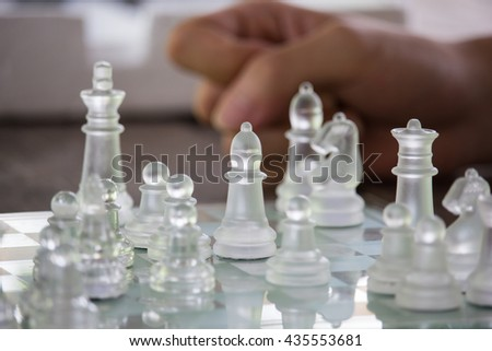 Transparent chess made fo glass on wood background , Focus sharp specific point - stock photo