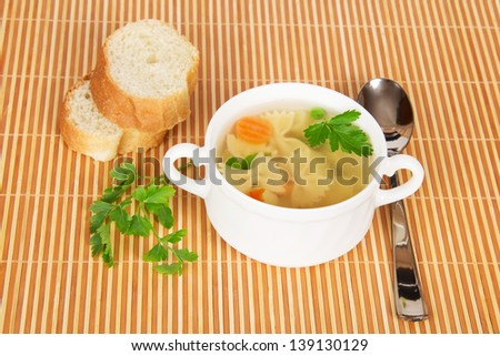 Transparent chicken broth with paste and vegetables on a bamboo cloth