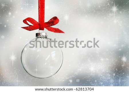 Transparent Christmas ball hanging on red ribbon on snowy winter background - stock photo
