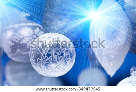 Transparent Christmas decoration with white ornament on blue background with lot of sparkles