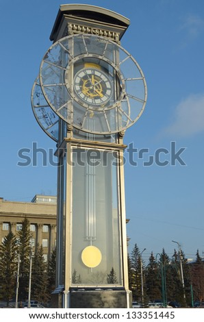 Transparent clock with a pendulum in a central square in Krasnoyarsk - stock photo