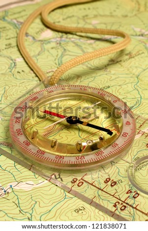 Transparent compass on the paper map.