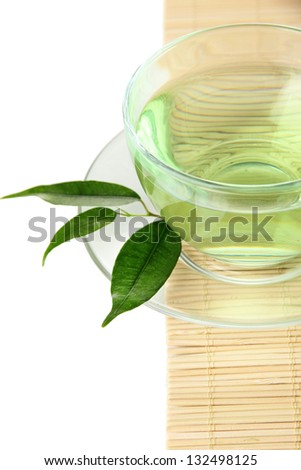 Transparent cup of green tea on bamboo mat, isolated on white - stock photo