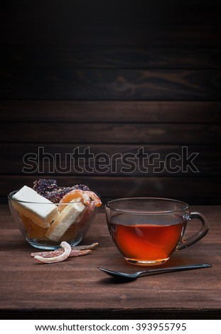 Transparent cup of tea and sweets on a wooden background