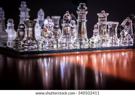 transparent glass chess board and figures with reflections - stock photo