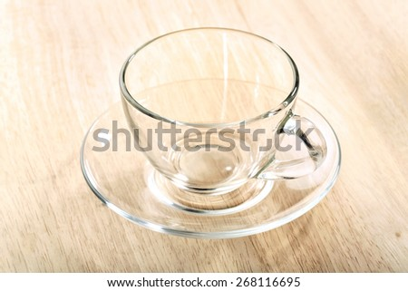 transparent glass cup and saucer close-up on wooden table - stock photo