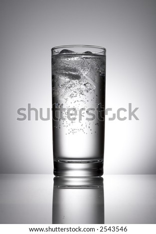Transparent glass filled with water and icecubes on neutral background reflected on table