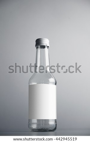 Transparent glass sealed empty bottle isolated on gray simple background with white blank label mockup - stock photo