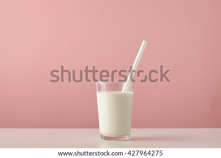 Transparent glass with fresh organic milk and white drinking straw inside isolated on pastel pink background on wooden table Space for your text above - stock photo