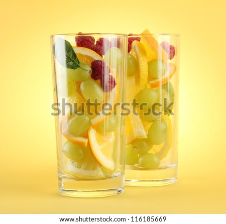 transparent glasses with citrus fruits, on yellow background