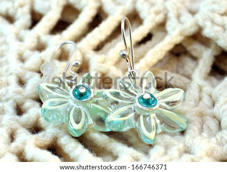 Transparent handmade earrings on the knitted background - stock photo