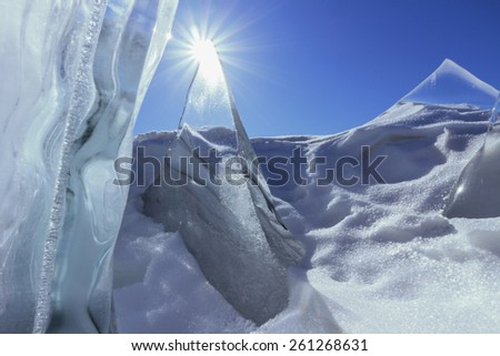 Transparent icicles and sun in blue sky outdoors - stock photo